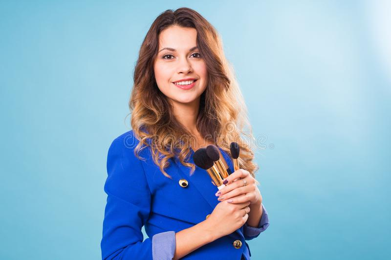 Beautiful make-up artist with brushes on blue background stock photography