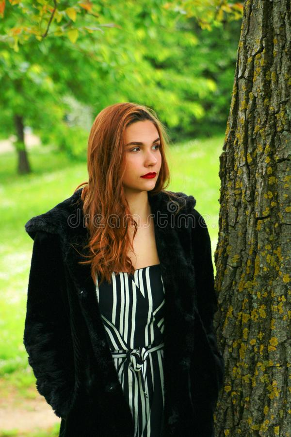 Beautiful makeup woman with a black fur coat. With long red hair and red lipstick royalty free stock photos