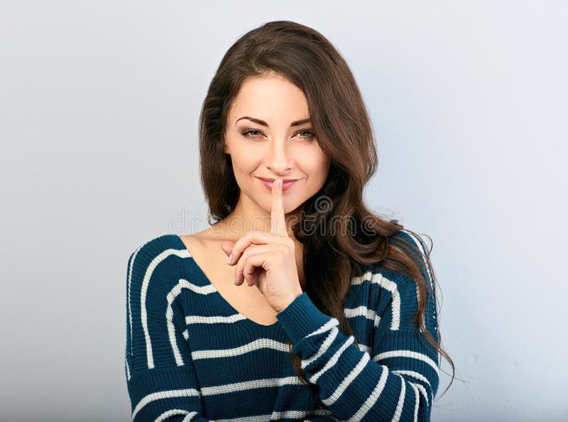 Beautiful makeup woman with long hair showing silence sign holding finger near the lips on blue background with empty copy space. stock photo