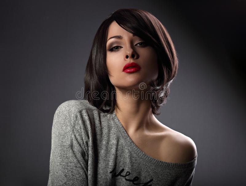 Beautiful makeup woman with short hair style and hot red lipstick posing with nude shoulder on dark shadow background. Close. Up portrait stock images