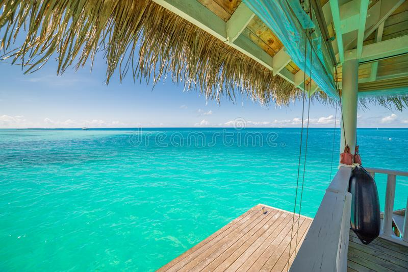 Overwater luxurious spa in the tropical blue lagoon of Maldives. Beautiful Maldives island beach landscape. Luxury resort with water bungalow and hut for summer royalty free stock image