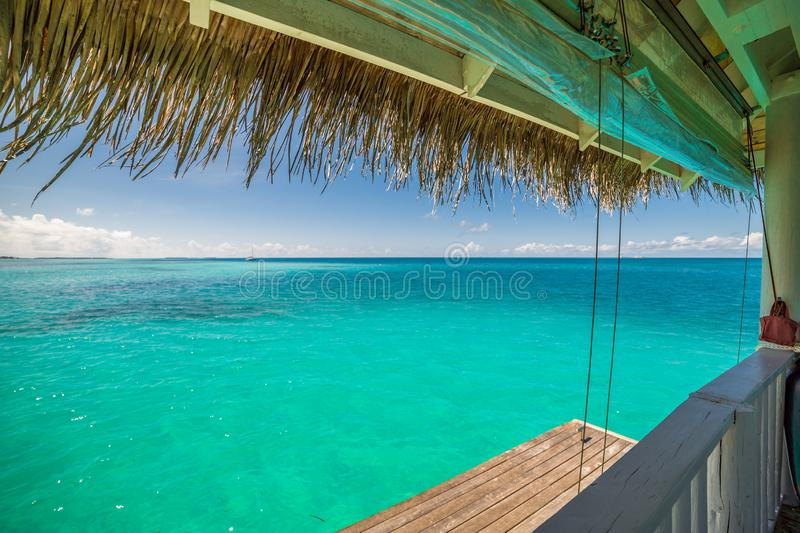 Overwater luxurious spa in the tropical blue lagoon of Maldives. Beautiful Maldives island beach landscape. Luxury resort with water bungalow and hut for summer stock image