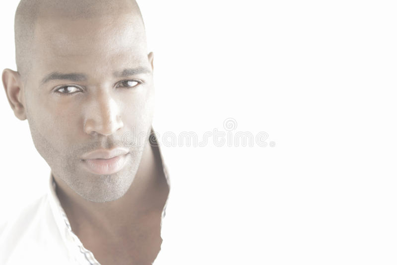 Beautiful male face in light. Very bright (high-key) portrait of a black male model against white background and lots of copy space stock images