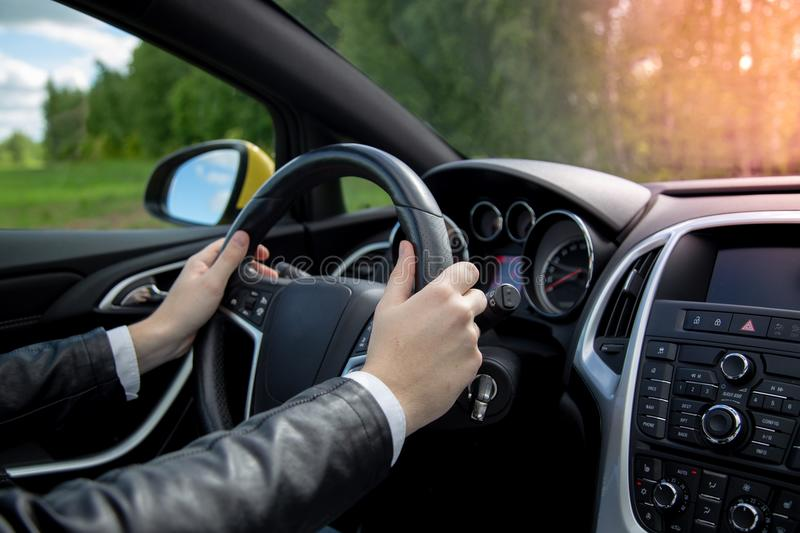 Beautiful male hands on steering wheel. Taxi driver businessman driving car on road trip wearing leather jacket and white shirt. Driving on a nostalgic road stock photo