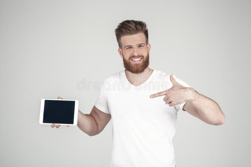 Beautiful man with a beard and a fashionable hairstyle dressed in casual clothing. Smilimg pointing by his finger on the tablet stock images