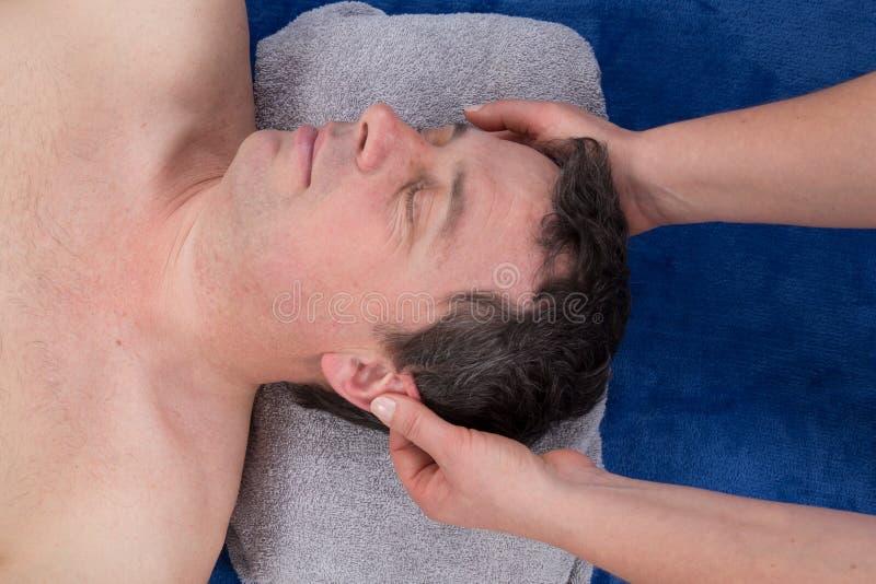 Beautiful man Getting a Face Treatment at Beauty Salon. Face Massage royalty free stock photo