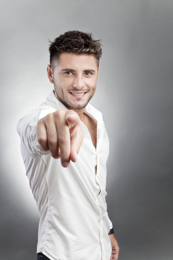 Beautiful man pointing. Beautiful man in white shirt pointing, studio background royalty free stock images