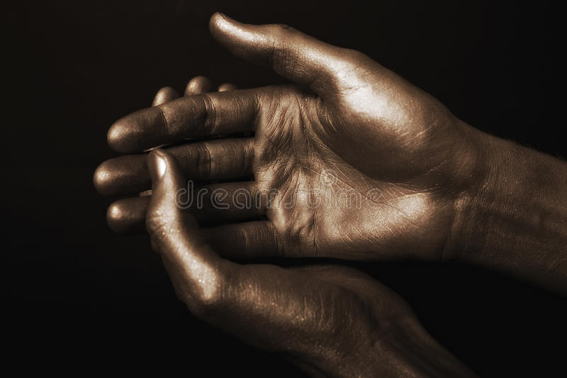 Beautiful man's hands in golden paint royalty free stock image