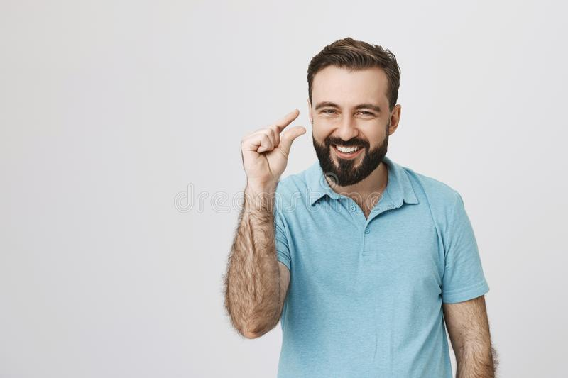 Beautiful man showing small thing while smiling and standing near white wall. Handsome bearded person in a blue shirt royalty free stock photo