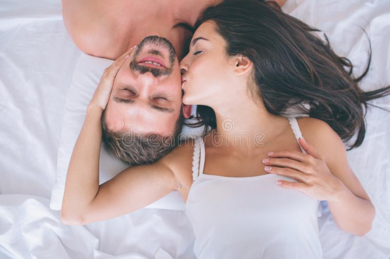 Beautiful man and woman are lying in white bed. Guy keeps eyes closed and smiles. Girl is touching his cheek and kissing royalty free stock images