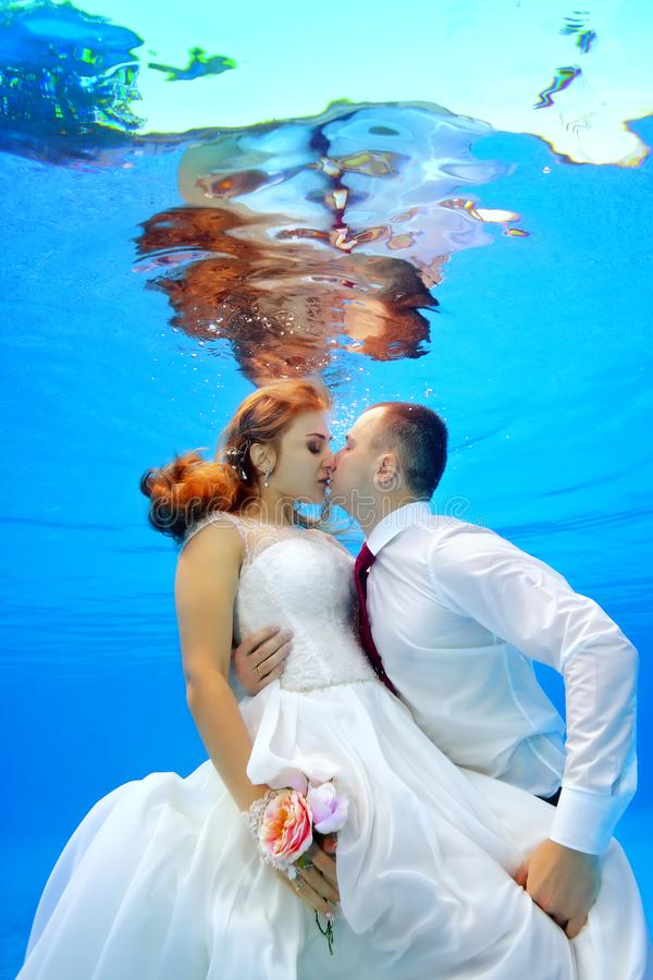 Beautiful man and woman in wedding dresses hugging and kissing underwater in the swimming pool on a background of sun rays stock photo