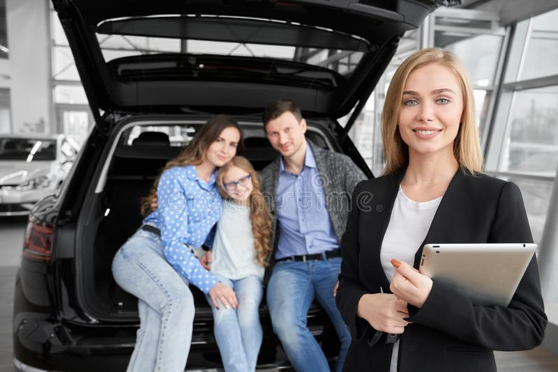 Beautiful manager of dealership and happy family posing. royalty free stock photos