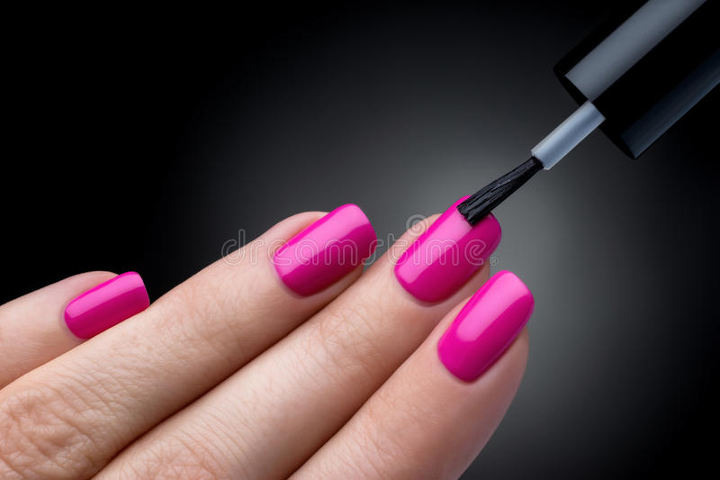 Beautiful manicure process. Nail polish being applied to hand, polish is a pink color. royalty free stock photography