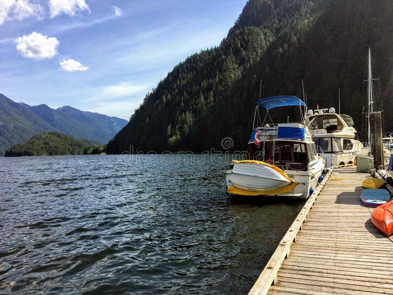 A beautiful marina full of boats and surrounded by forests and mountains in a remote inlet in Indian Arm, outside Vancouver. British Columbia, Canada.  The royalty free stock photography