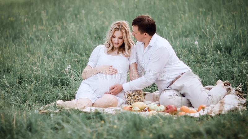 Beautiful married couple sitting on the grass during picnic royalty free stock photo