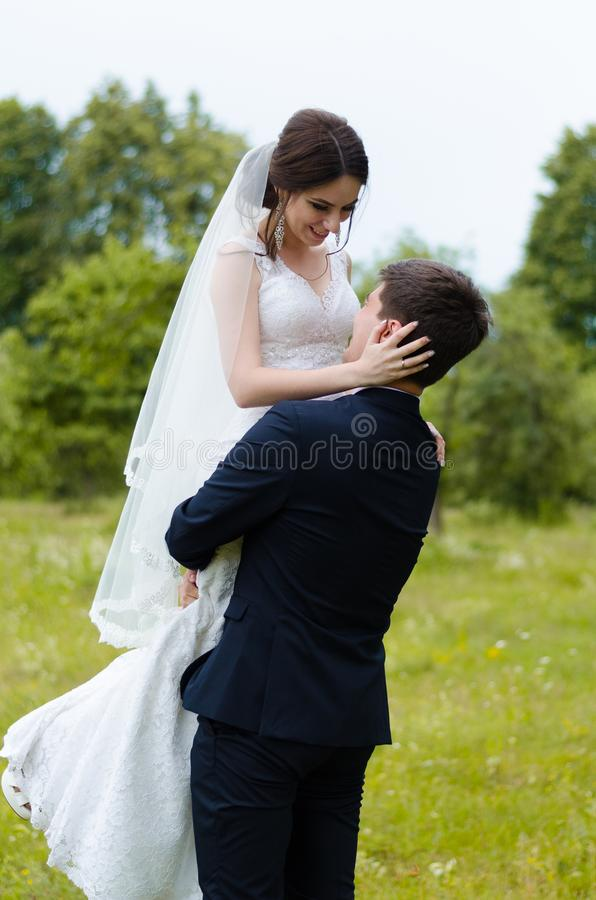 A beautiful married couple in wedding dresses, posing for a photo shooting in an belarusian village. Green background royalty free stock photography