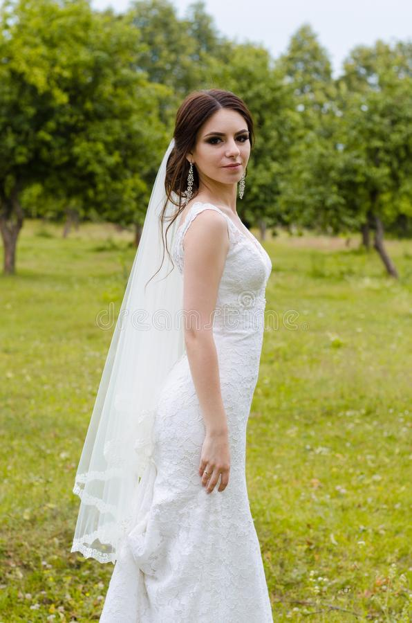 A beautiful married girl in wedding dress, posing for a photo shooting in an belarusian village. Green background royalty free stock photography