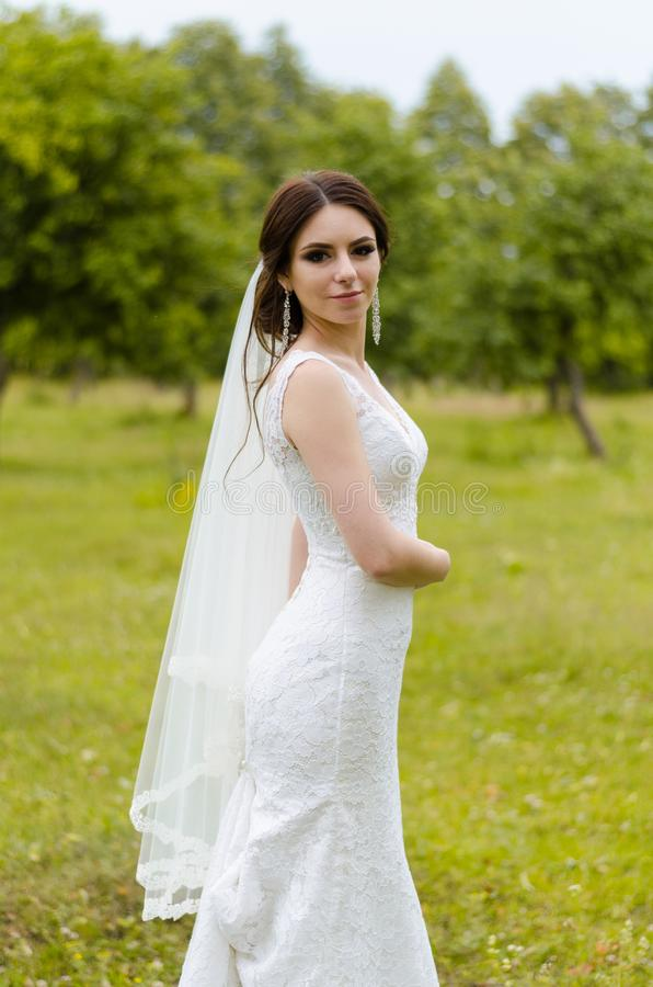 A beautiful married girl in wedding dress, posing for a photo shooting in an belarusian village. Green background stock image