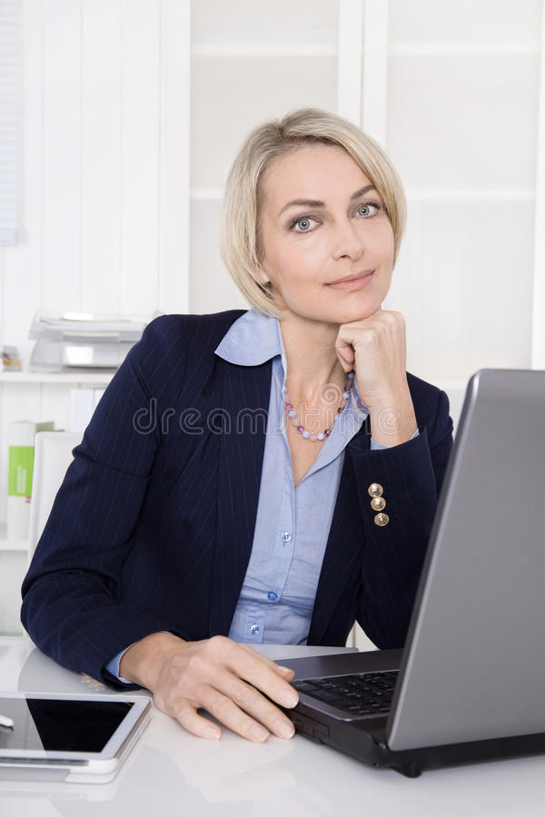 Beautiful mature business woman in her office. royalty free stock photo