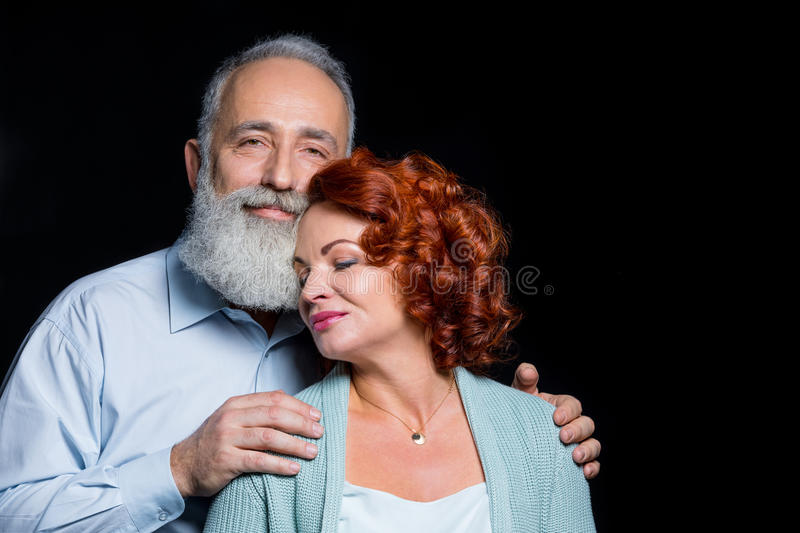 Beautiful mature couple. Beautiful happy mature couple in love embracing on black stock photos