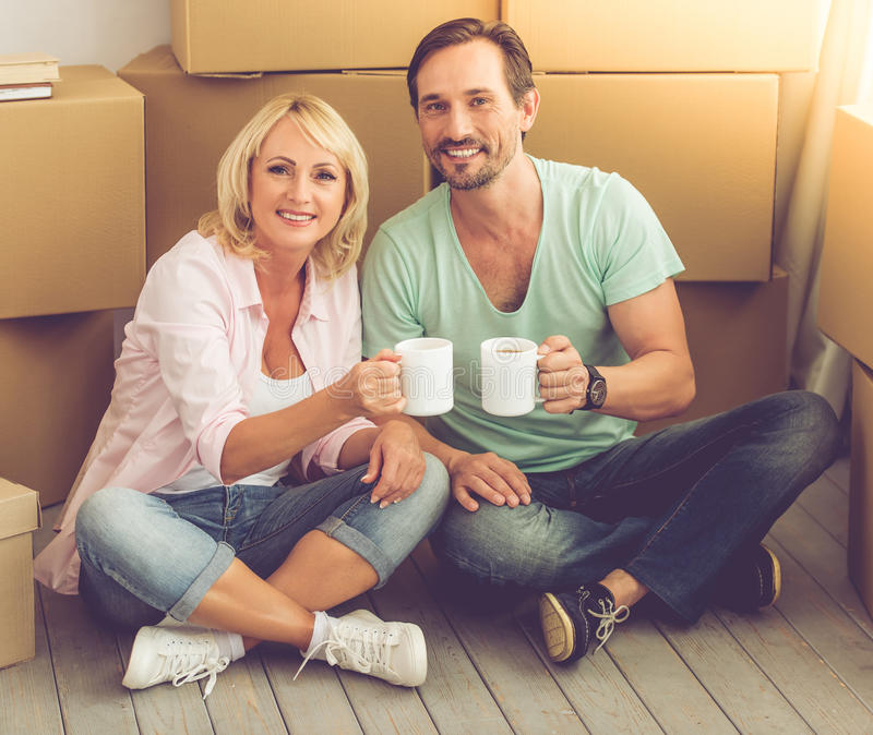 Beautiful mature couple moving. Beautiful mature couple in casual clothes is drinking coffee, looking at camera and smiling while sitting on the floor among stock images