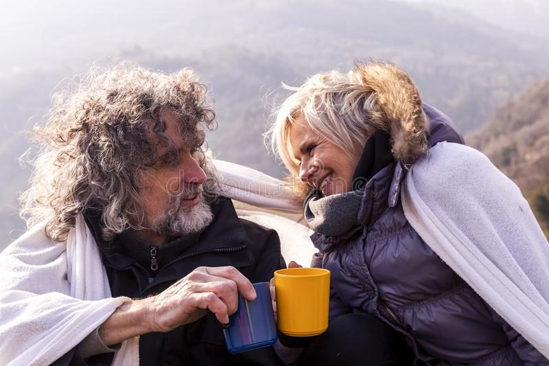 Beautiful mature couple relaxing and drinking hot coffee royalty free stock photo
