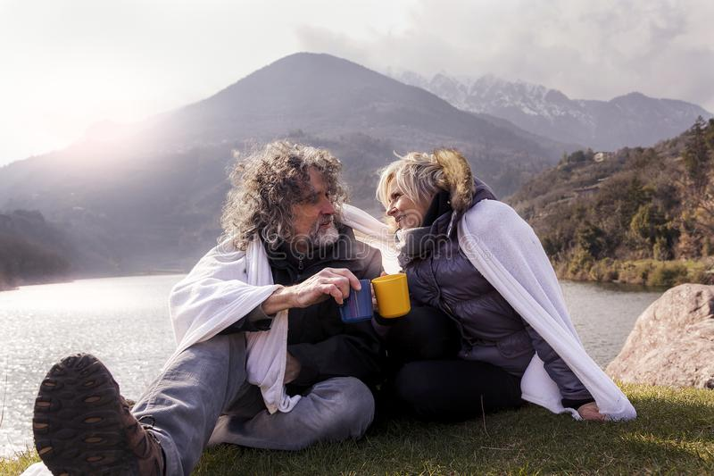 Beautiful mature couple relaxing and drinking hot coffee stock image