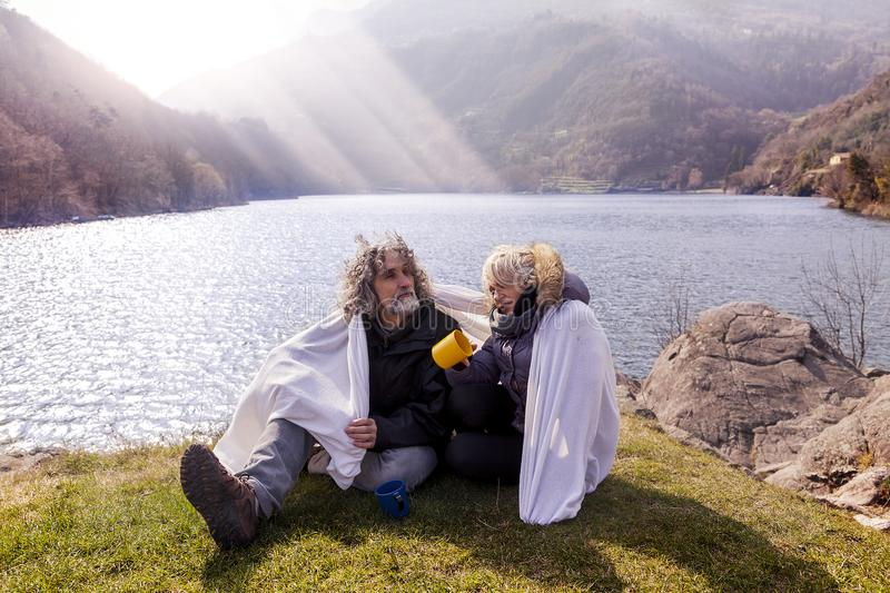 Beautiful mature couple relaxing and drinking hot coffee royalty free stock images