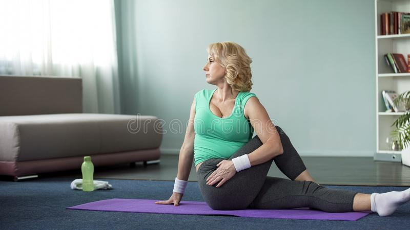 Beautiful mature female practicing twisting sage pose at home, yoga time, sport royalty free stock photos