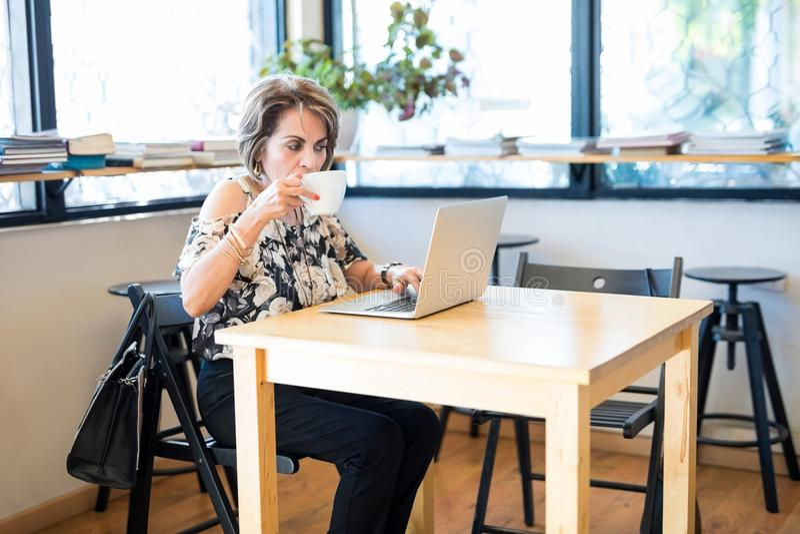 Mature hispanic woman working from cafe stock photo