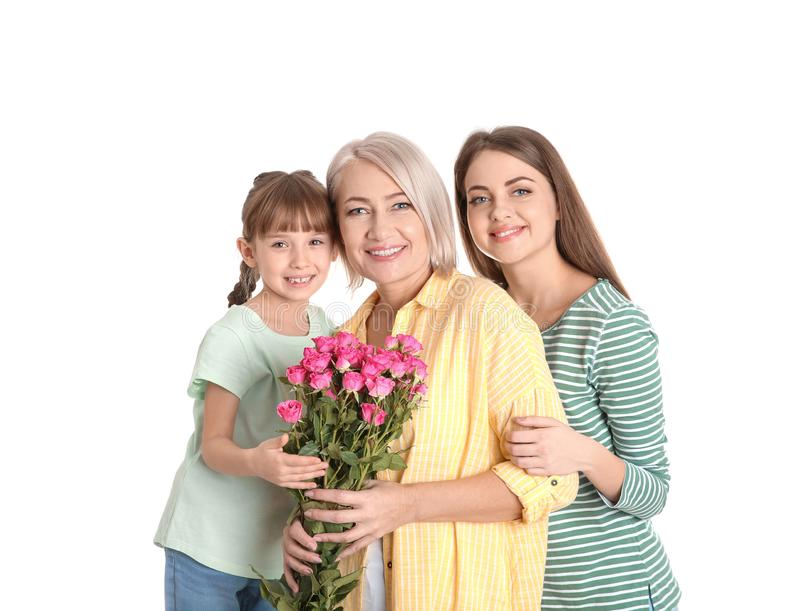 Beautiful mature lady, daughter and grandchild with flowers on white. Happy Women`s Day stock photo