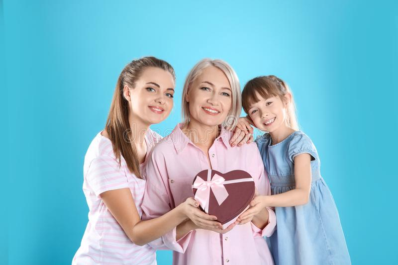Beautiful mature lady, daughter and grandchild with gift on color background stock image