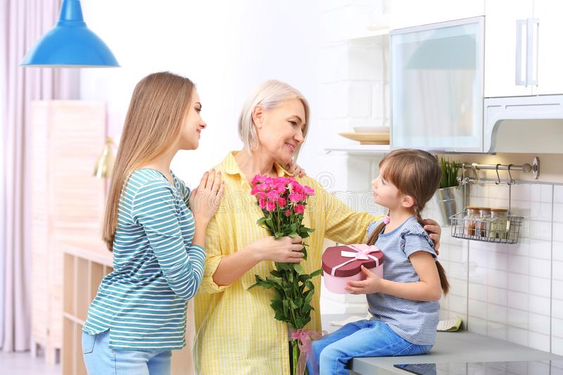 Beautiful mature lady, daughter and grandchild with gifts in kitchen stock photo