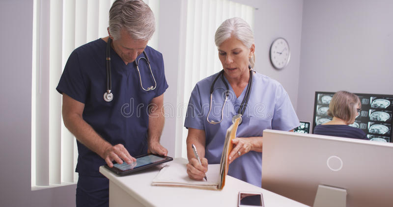 Beautiful mature nurse writing notes in patient file with male colleague stock photography