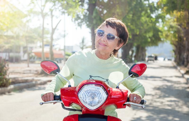 Beautiful mature stylish woman on motobike on a summer day, active pension and travel stock photos