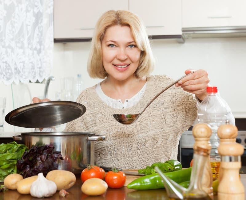 Beautiful mature woman cooking soup stock photo