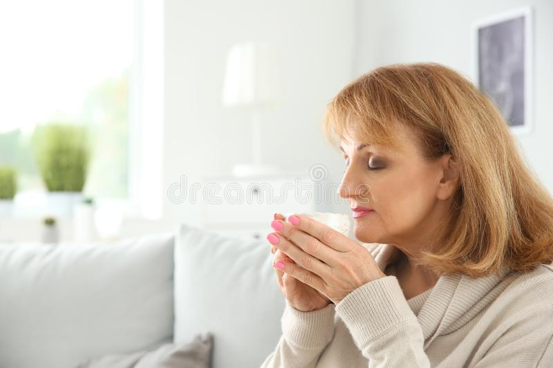 Beautiful mature woman drinking coffee at home royalty free stock image
