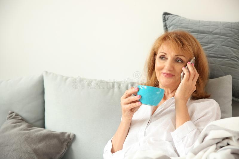 Beautiful mature woman drinking coffee while talking by phone at home royalty free stock photography