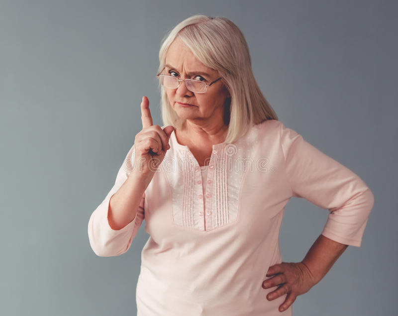 Beautiful mature woman. In eyeglasses is warning and looking at camera, on gray background royalty free stock photo