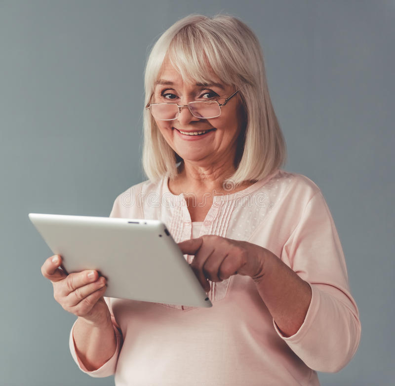 Beautiful mature woman with gadget. Beautiful mature woman in eyeglasses is using a digital tablet, looking at camera and smiling, on gray background stock images