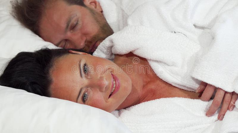 Beautiful mature woman going to sleep with her husband at home stock photo