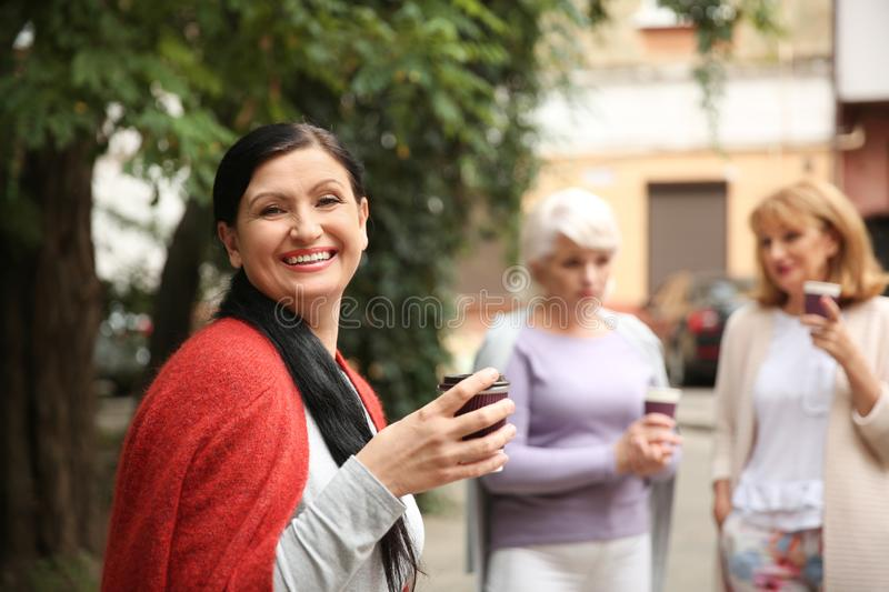 Beautiful mature woman and her friends drinking coffee outdoors stock photography