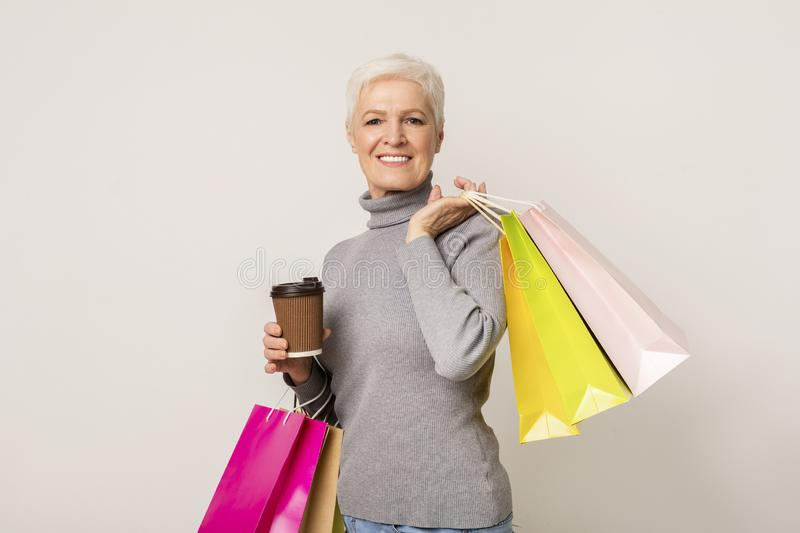 Beautiful mature woman holding cup of coffee and bright shopping bags stock photos