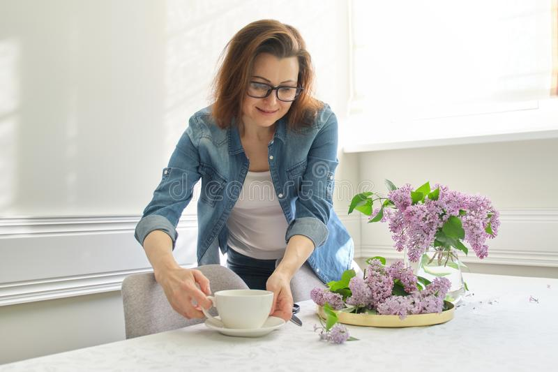 Beautiful mature woman at home with bouquet of lilac flowers in vase drinking cup of coffee stock images