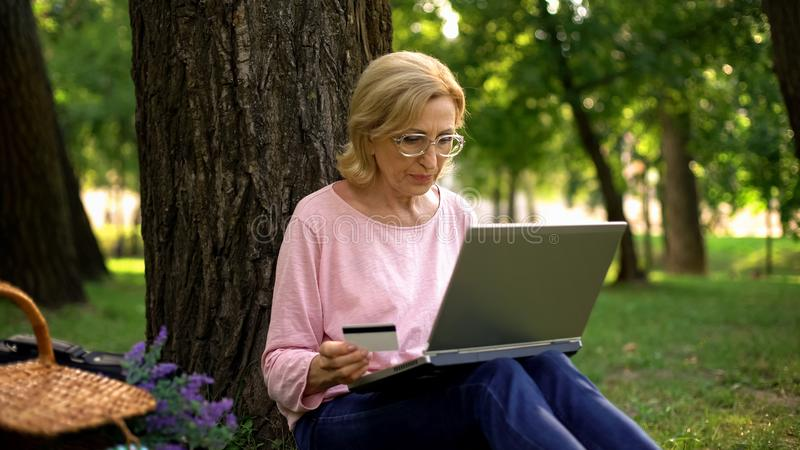 Beautiful mature woman inserting card number on laptop pc in park, shopping stock image