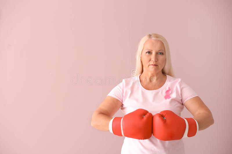 Beautiful mature woman with pink ribbon and boxing gloves on color background. Breast cancer concept stock photos
