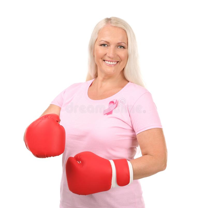 Beautiful mature woman with pink ribbon and boxing gloves on white background. Breast cancer concept royalty free stock images