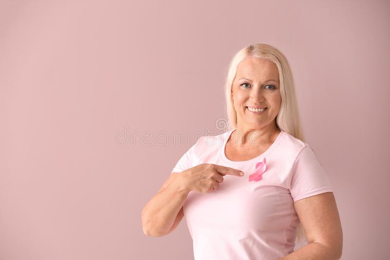 Beautiful mature woman with pink ribbon on color background. Breast cancer concept royalty free stock photo
