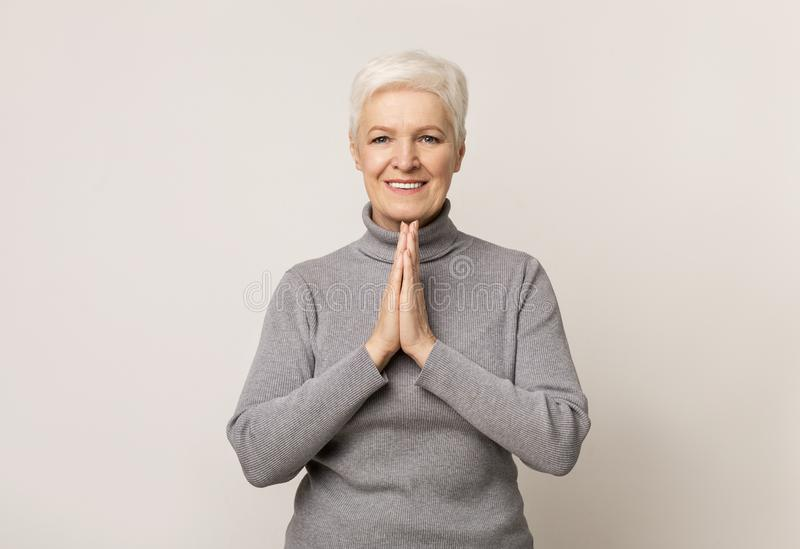 Beautiful mature woman pleading for something with clasped hands royalty free stock photo