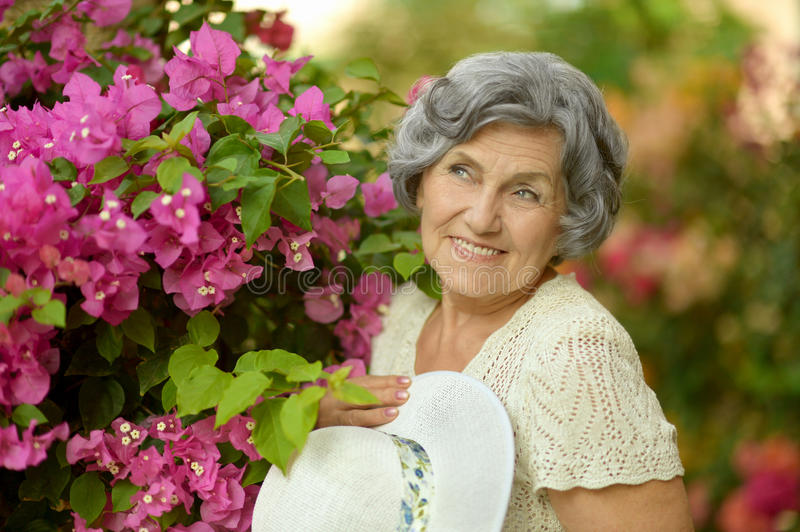 Beautiful mature woman. Posing with flowers outdoors stock photography